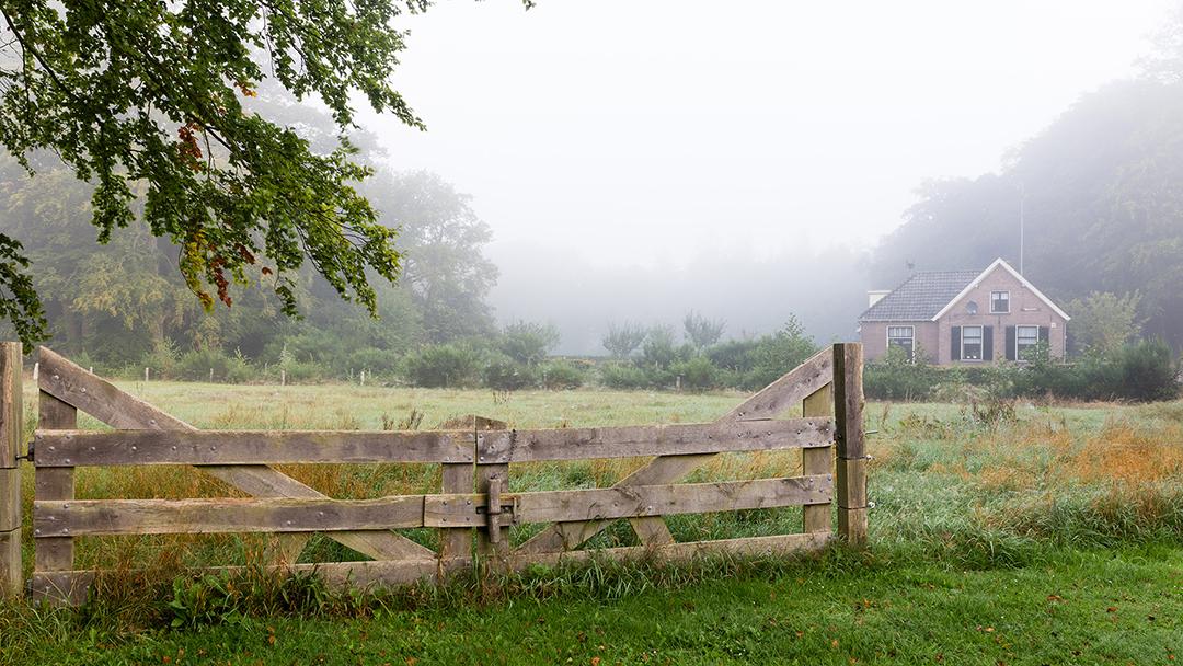 Tuinmanshuis met hek op voorgrond